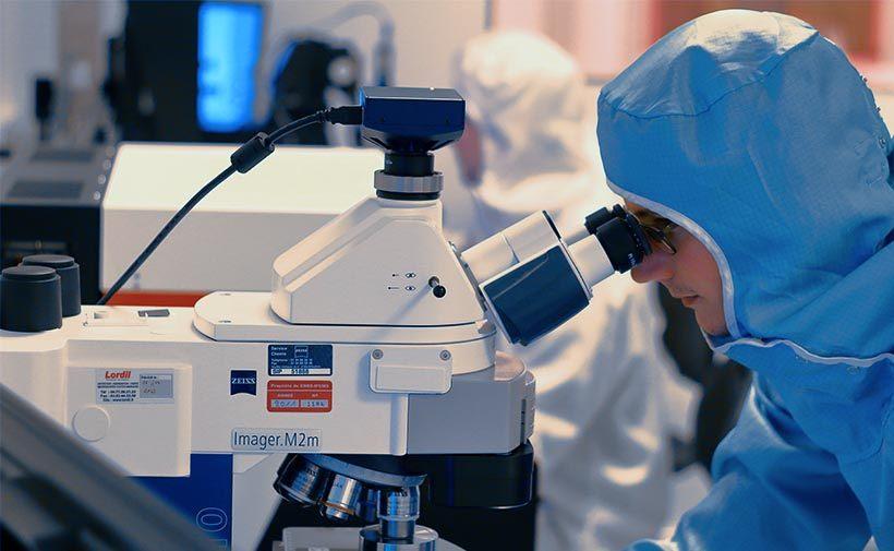 Onderzoeker met microscoop in cleanroom