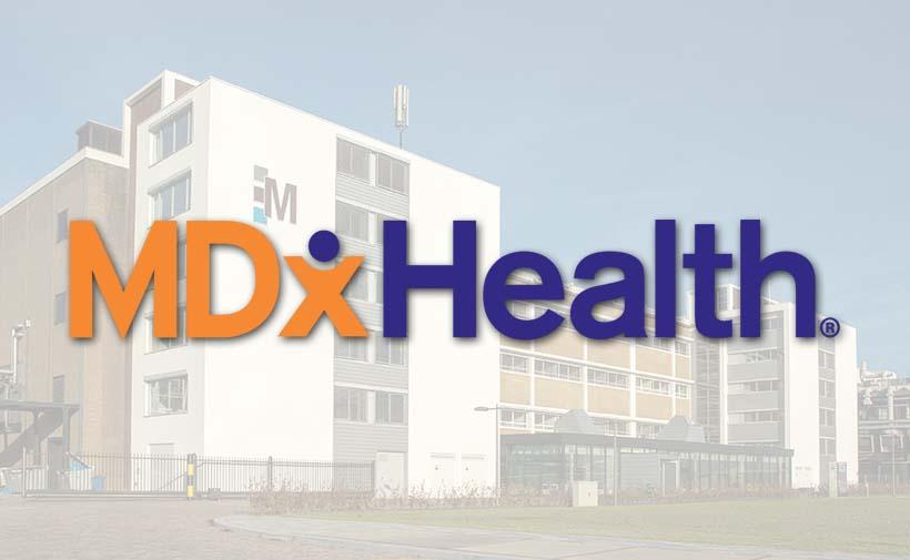 Het logo van MDxHealth met Gebouw M op Novio Tech Campus op de achtergrond
